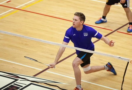 Badminton player Sam White lunges for the shuttle in a doubles match.