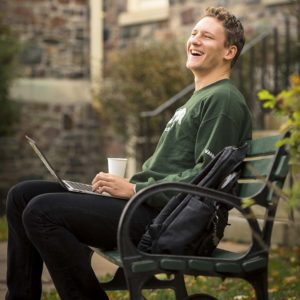 Benn Van Ryn using his laptop in the King's quad