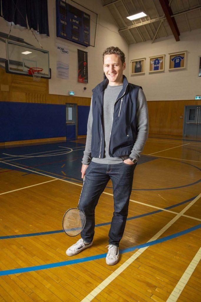 Benn Van Ryn in the gymnasium holding a badminton racquet.